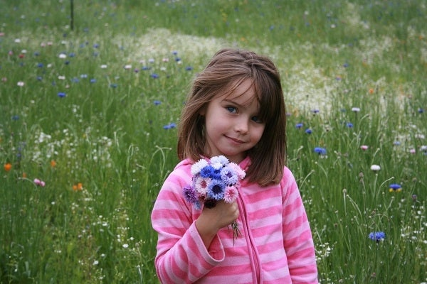Young girl holding handheld bouquet made of different color Cornflowers