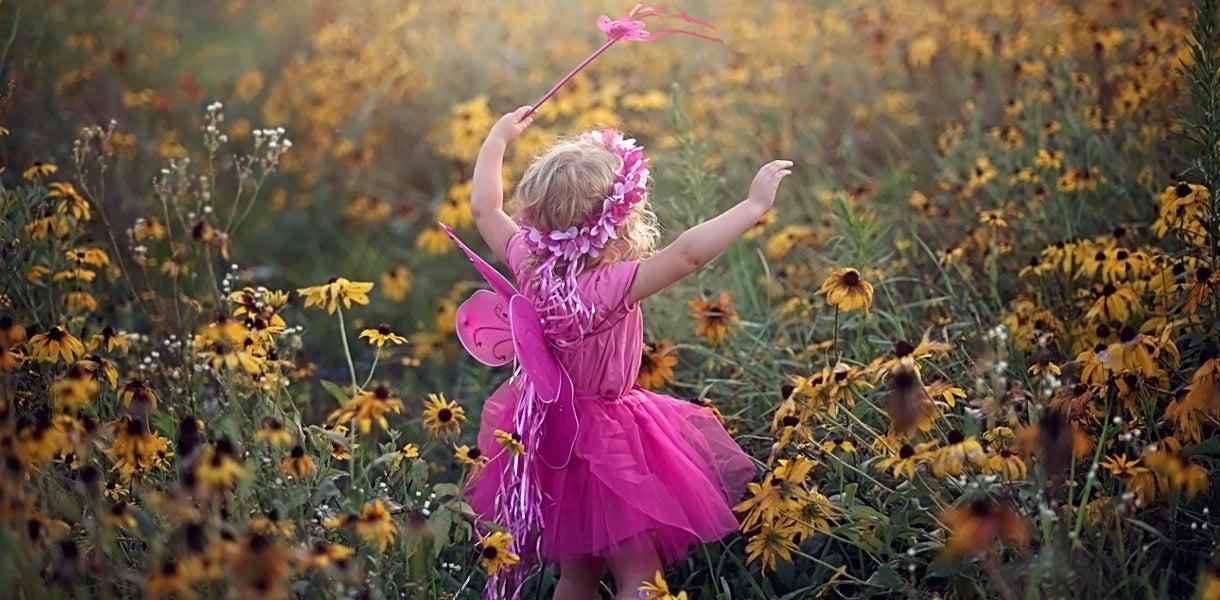girl running through a field of black eyed susans