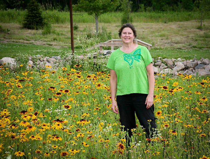 woman standing in a field of black eyed susans